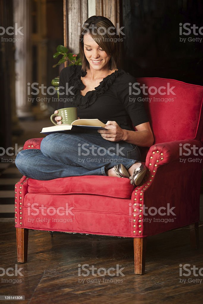 Mature women curled up with a good book and coffee stock photo