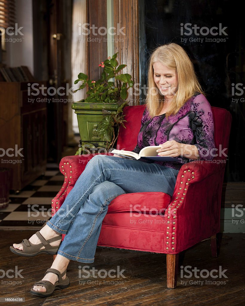 Mature women curled up with a good book stock photo