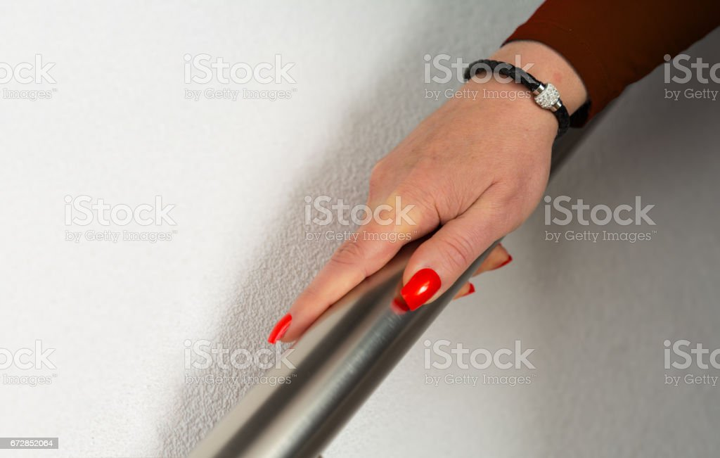 Mature women descending stairs with focus on her hand stock photo
