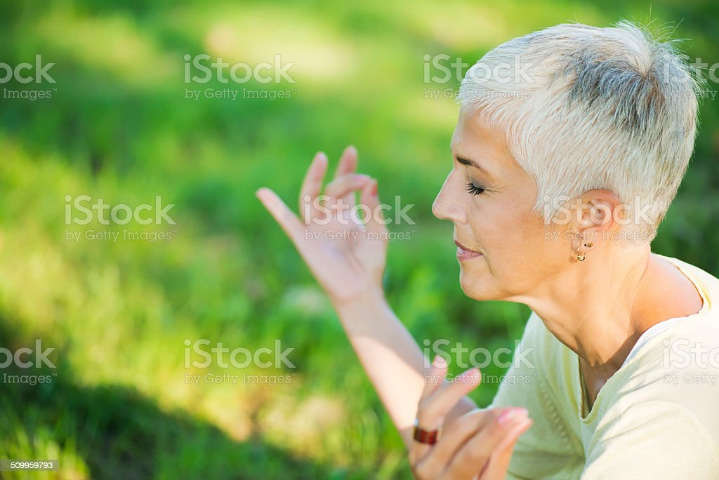 Mature women practising yoga in the meadow stock photo