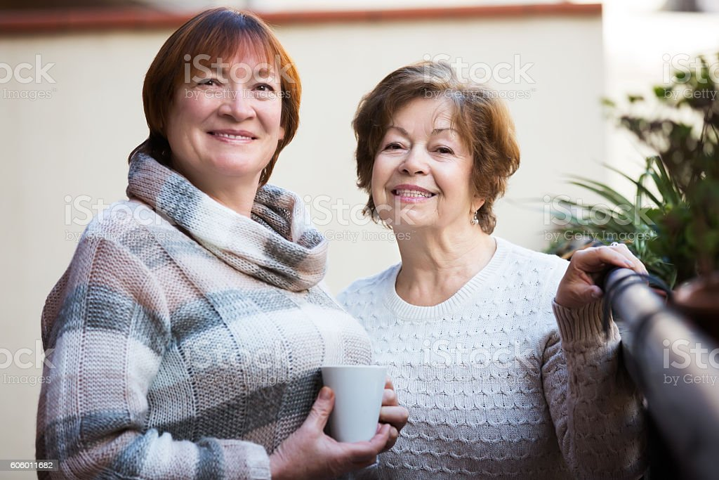 Mature women talking at patio stock photo