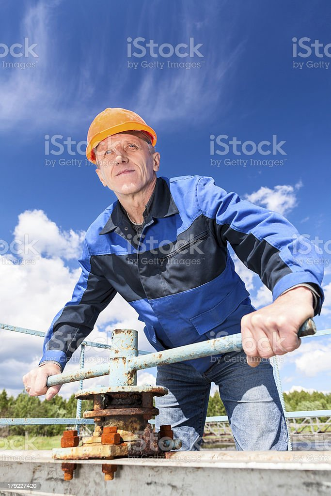 Mature worker in hardhat at factory with the pipe valve royalty-free stock photo