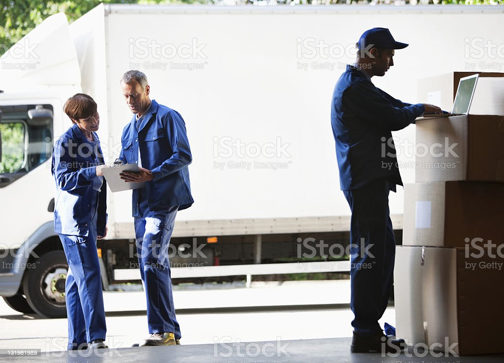 Mature workers discussing while young man using laptop in warehouse stock photo