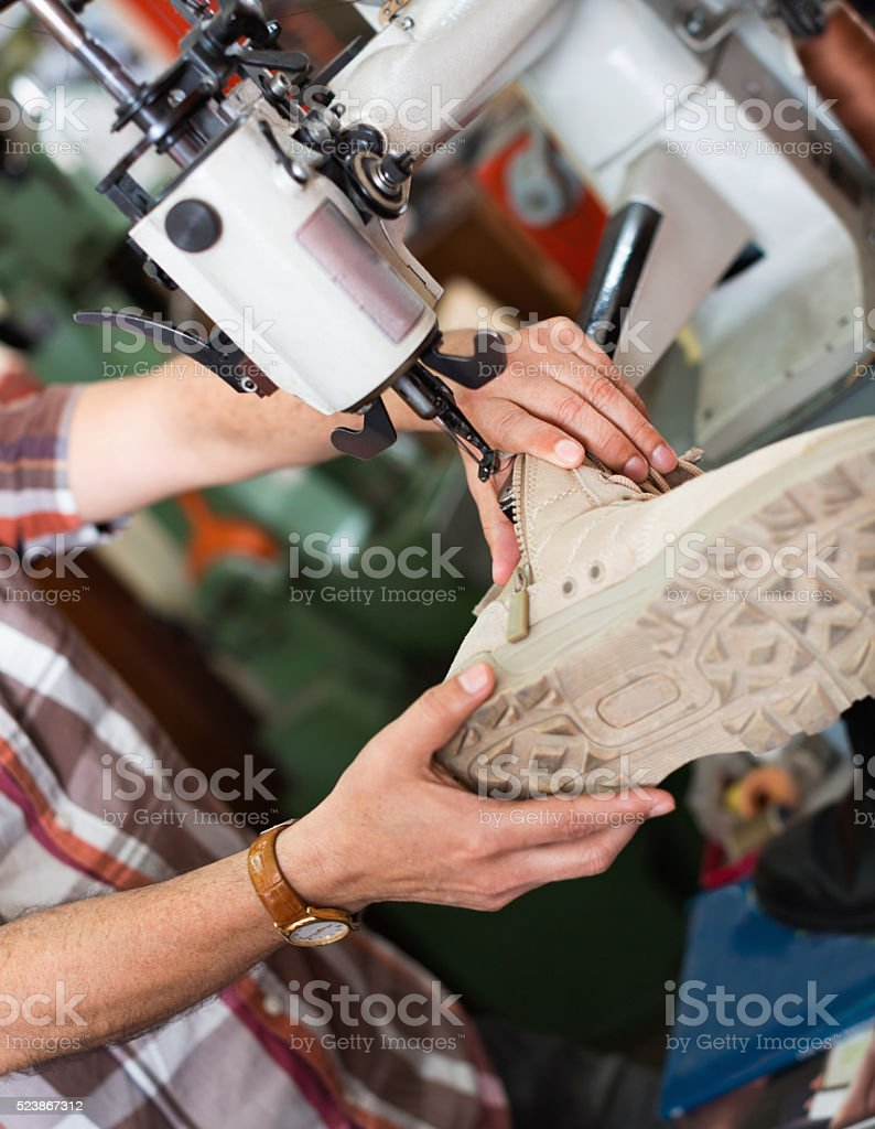 Mature  workman sewing leather boots on stitch lathe stock photo
