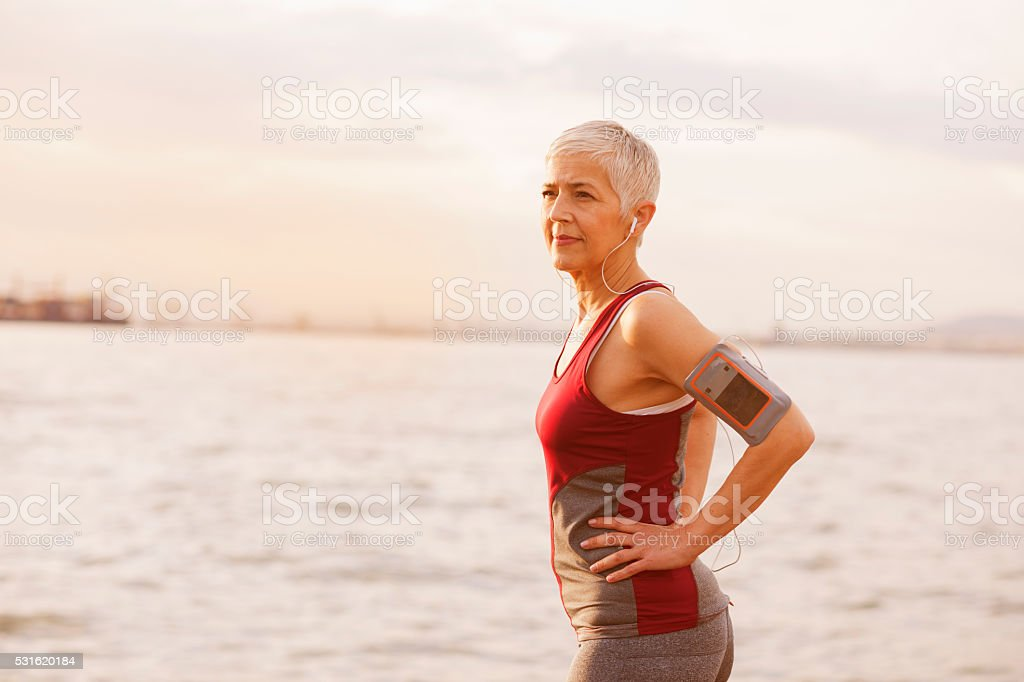 Mature-senior woman jogging beside the sea stock photo