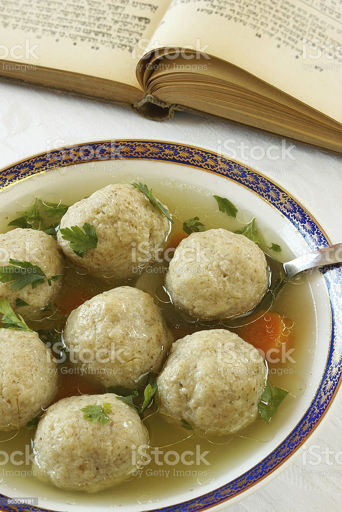 Matzah ball soup in a bowl with spoon stock photo