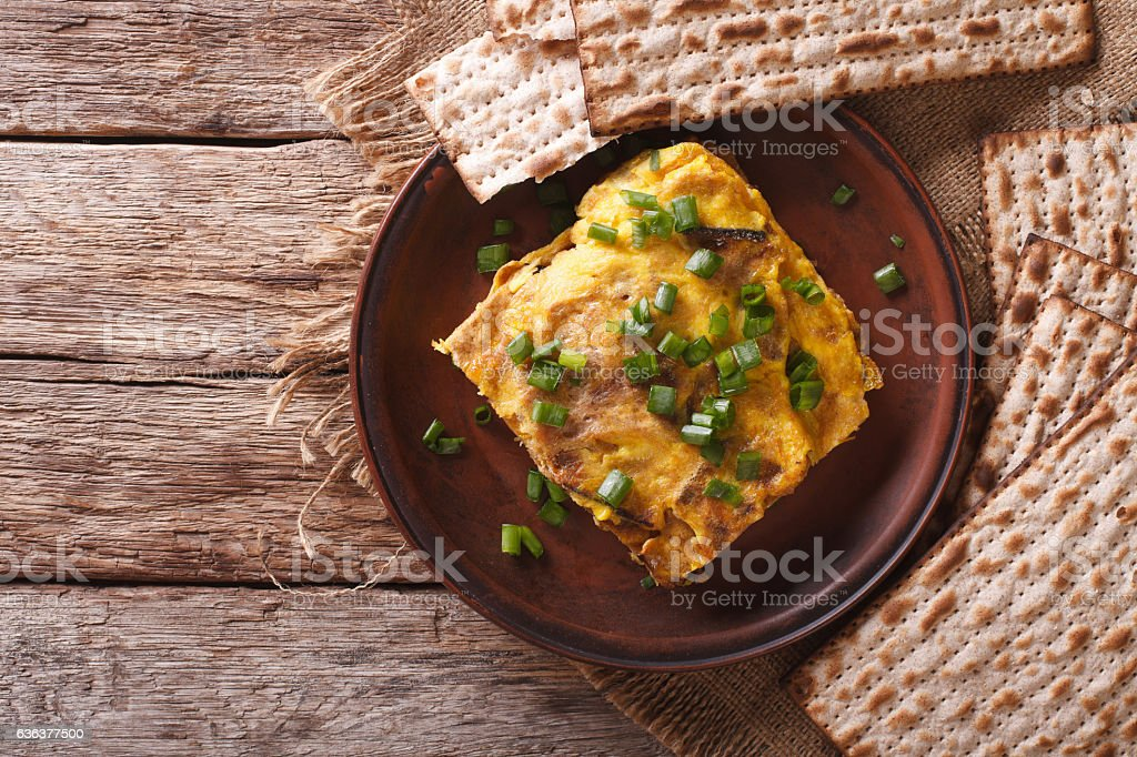 Matzah brei with green onions close-up on a plate. horizontal stock photo