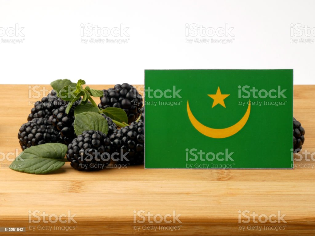 Mauritania flag on a wooden panel with blackberries isolated on a white background stock photo