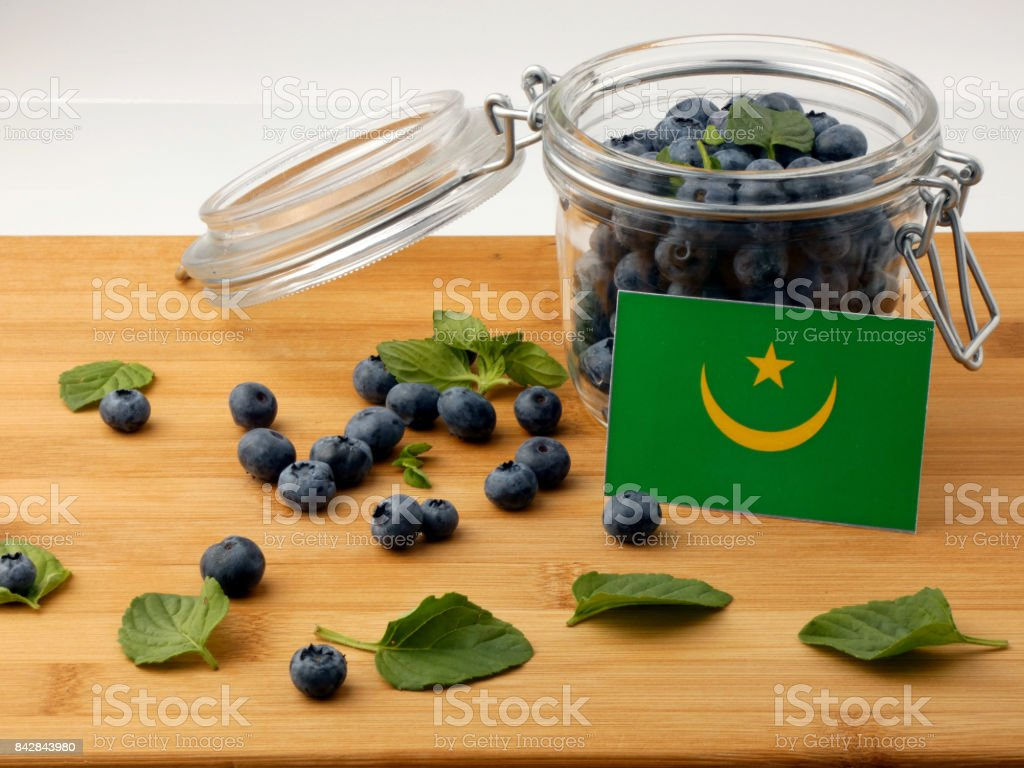 Mauritania flag on a wooden plank with blueberries isolated on white stock photo