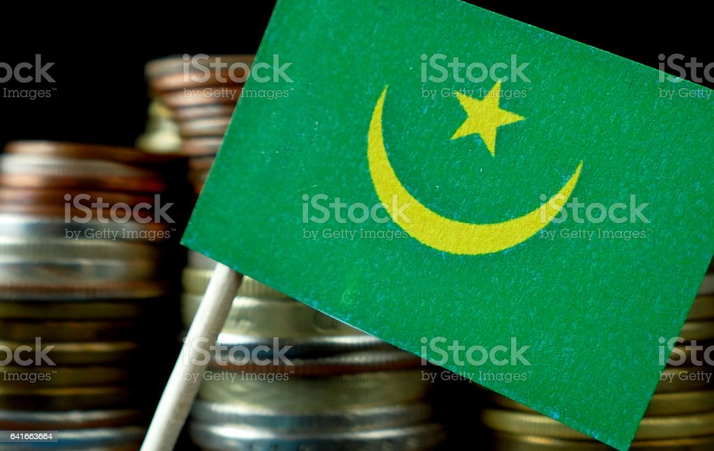 Mauritania flag waving with stack of money coins macro stock photo