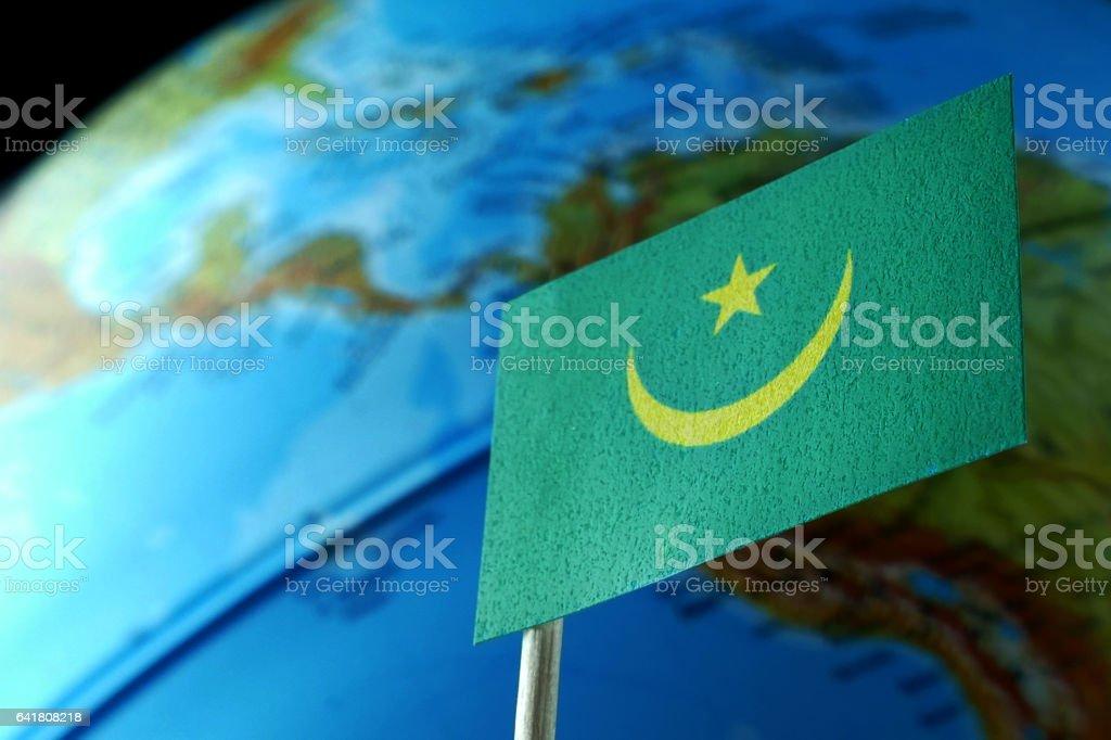 Mauritania flag with a globe map as a background macro stock photo