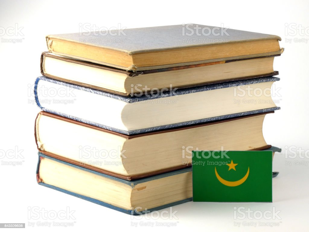 Mauritania flag with pile of books isolated on white background stock photo