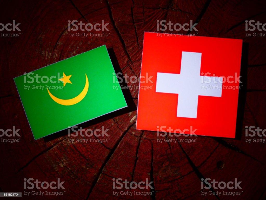 Mauritania flag with Swiss flag on a tree stump isolated stock photo