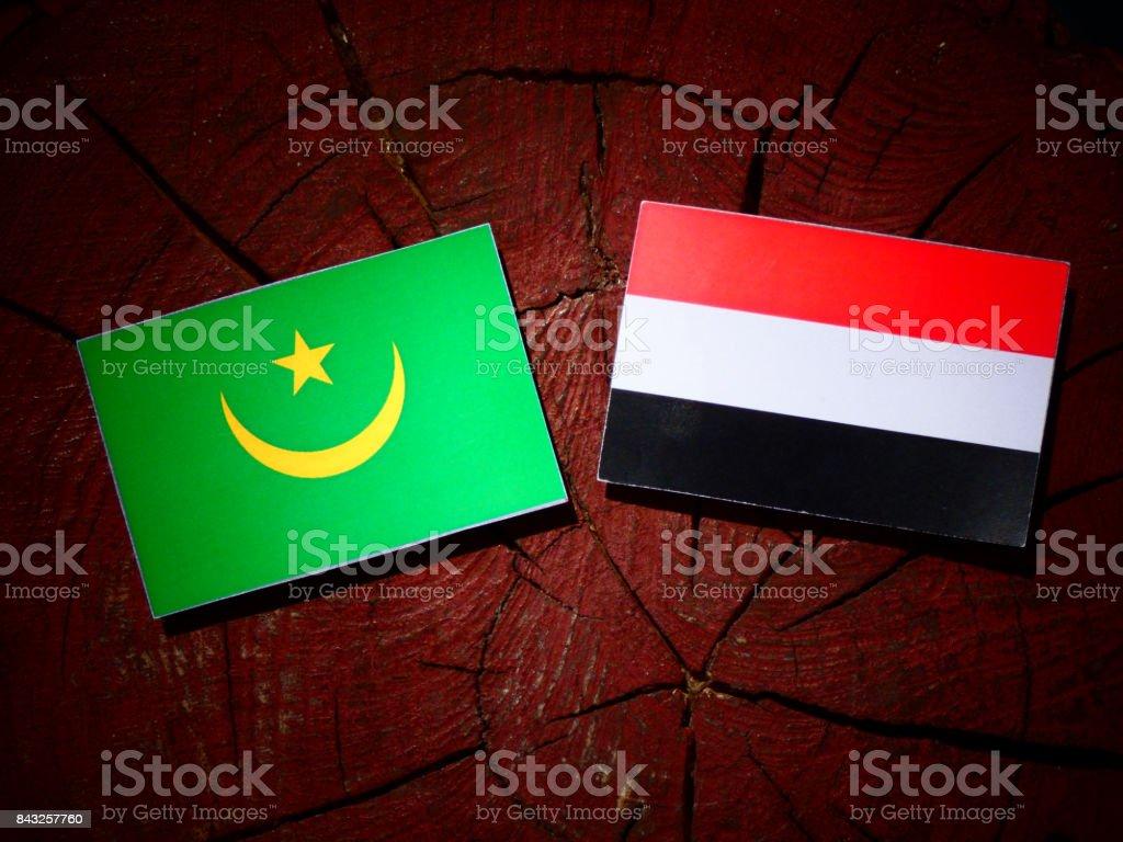 Mauritania flag with Yemeni flag on a tree stump isolated stock photo