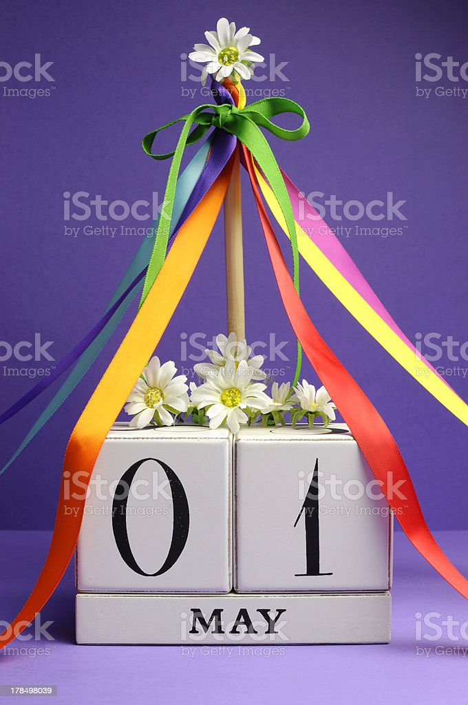 May Day white block calendar with maypole and colorful ribbons. stock photo