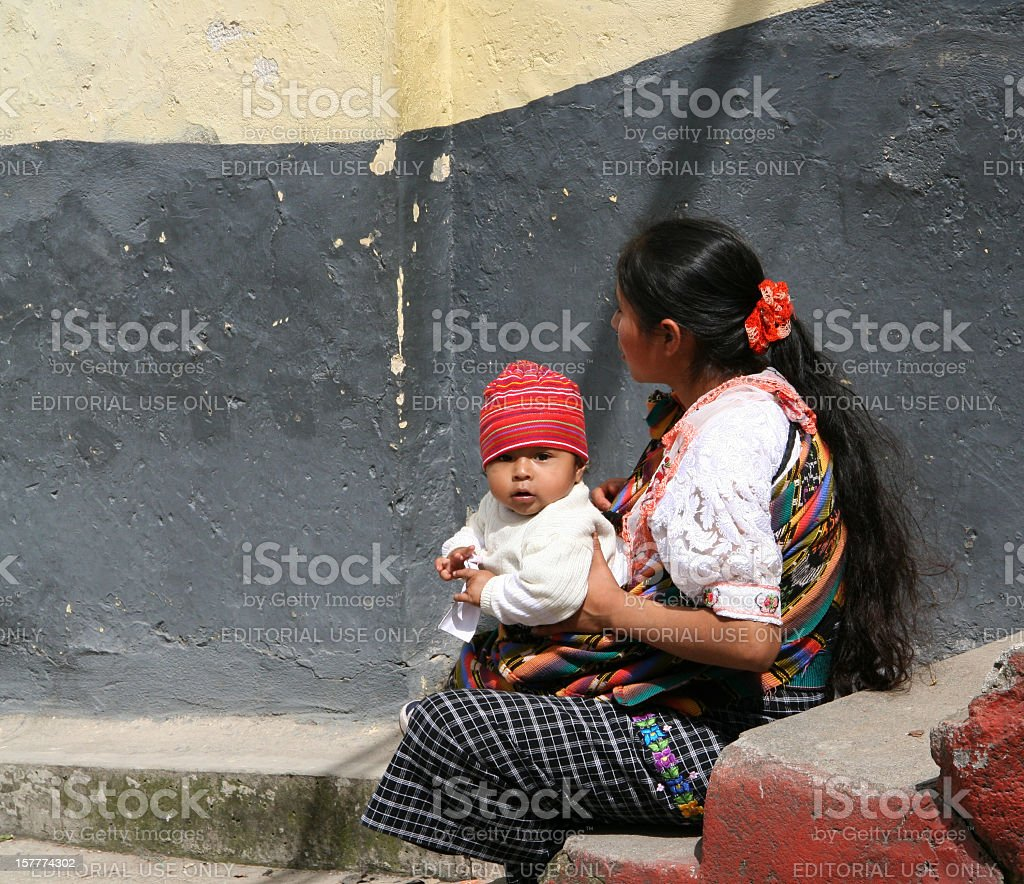 Mayan woman sitting by a wall with her little son stock photo