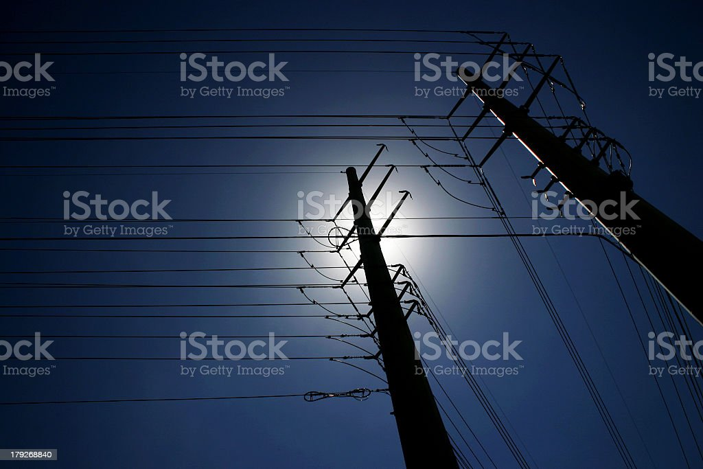 Maze of power lines against deep blue sky stock photo