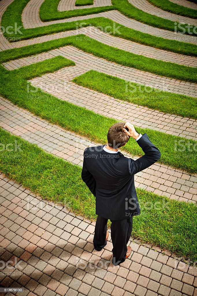 Maze with Confused Businessman Pondering Strategic Path and Occupation Solutions stock photo