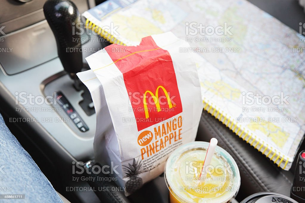 McDonald's Breakfast Bag and Orange Juice in Car With Roadmap royalty-free stock photo