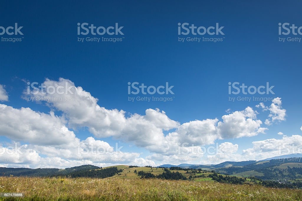 meadow, mountain and sky with clouds stock photo