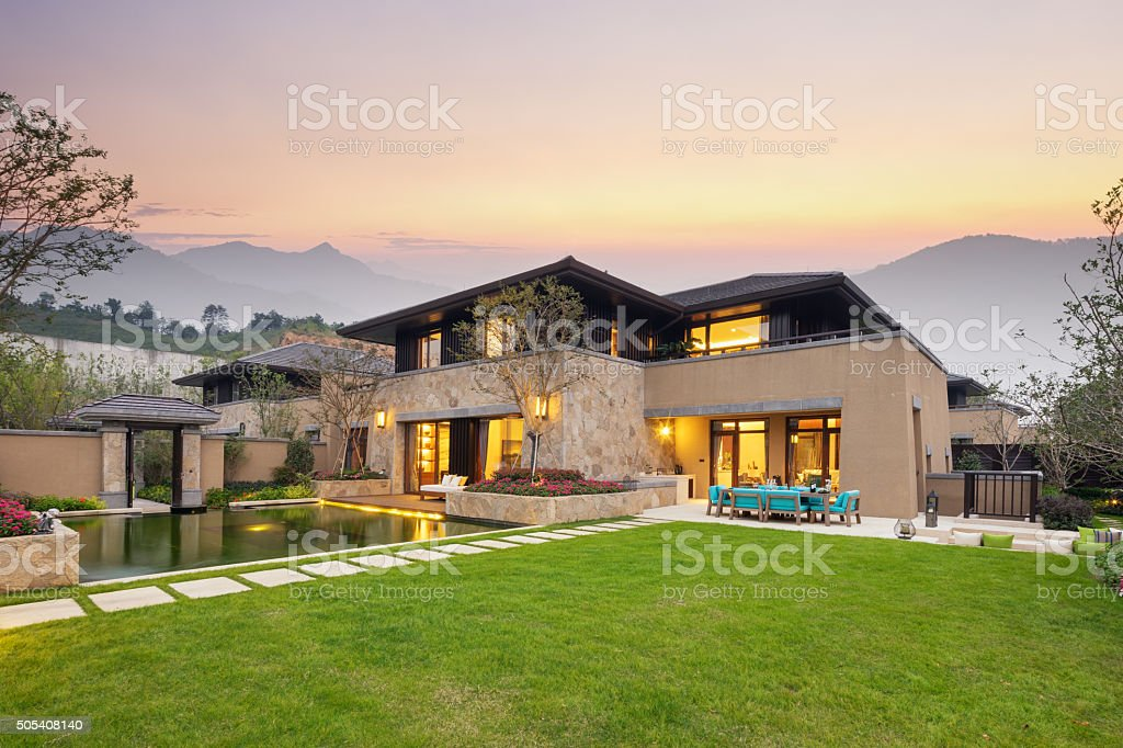 meadow near pond in modern buildings at twilight stock photo