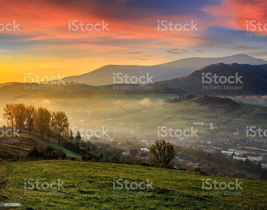meadow near village in autumn mountains at sunrise stock photo
