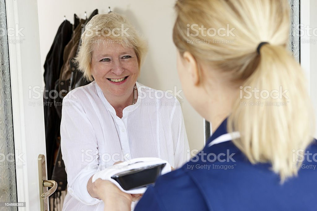 meal being delivered to senior woman at home royalty-free stock photo