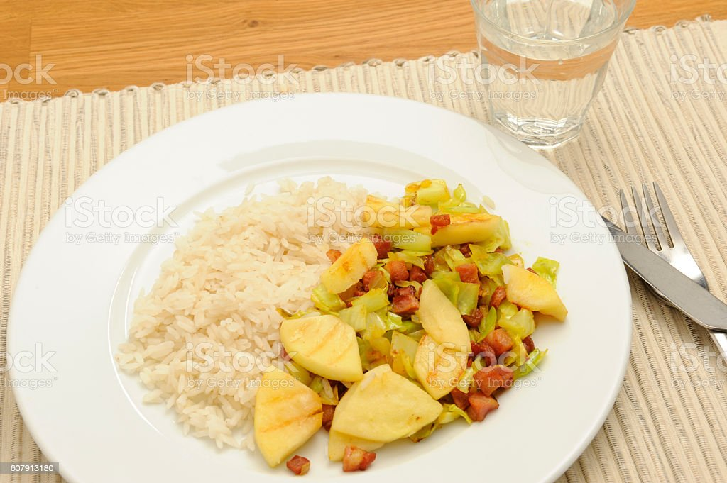 Meal with bacon, oxheart cabbage, apple and white rice stock photo