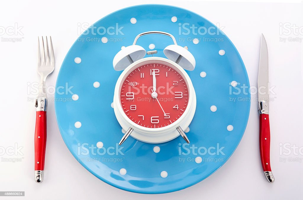 Mealtime table place setting with alarm clock stock photo