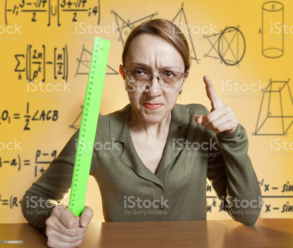 Mean female teacher holding ruler and pointing her finger royalty-free stock photo