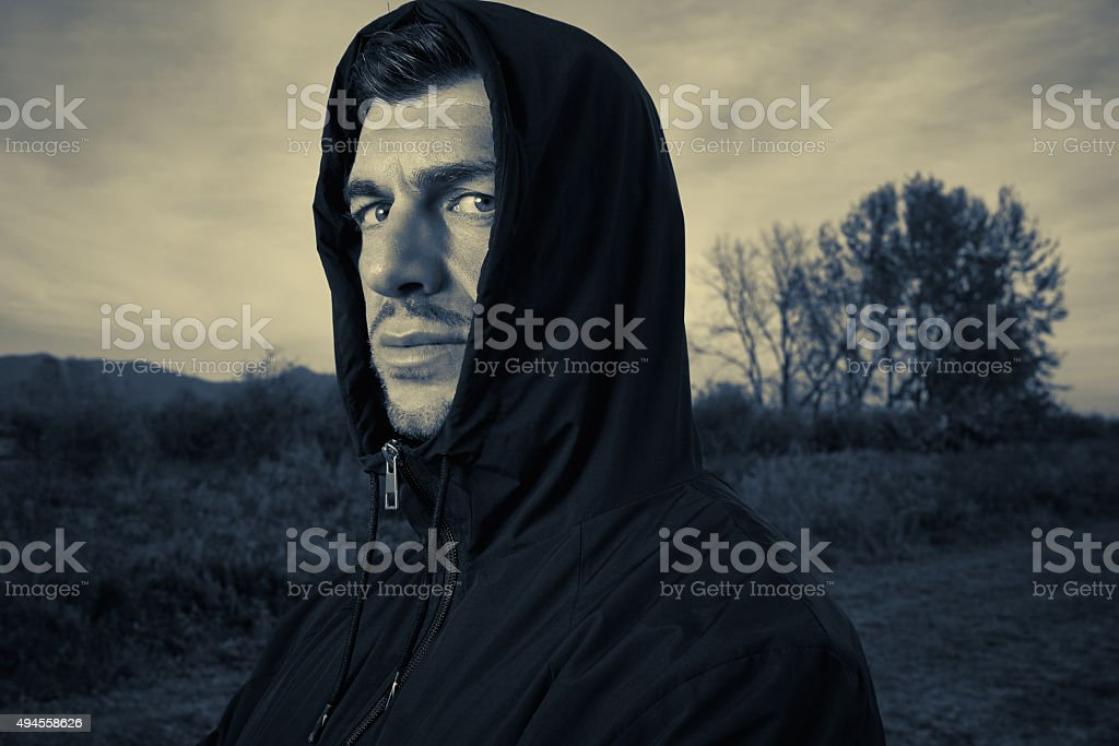 Mean hooded man looking at you - be afraid! stock photo