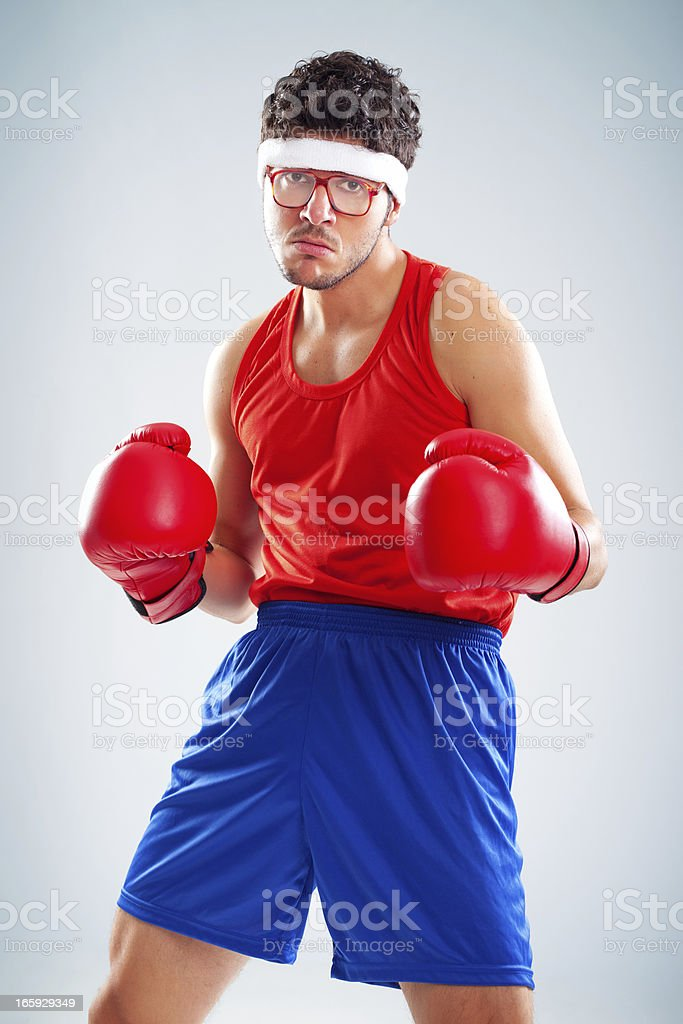 Mean nerdy boxer posing with his red boxing gloves royalty-free stock photo