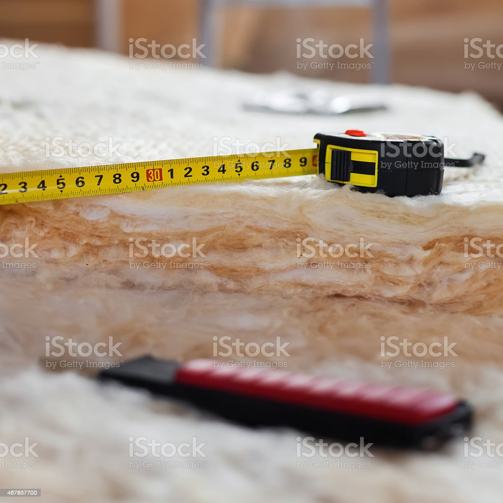 Measure tape and knife on mineral wool stock photo