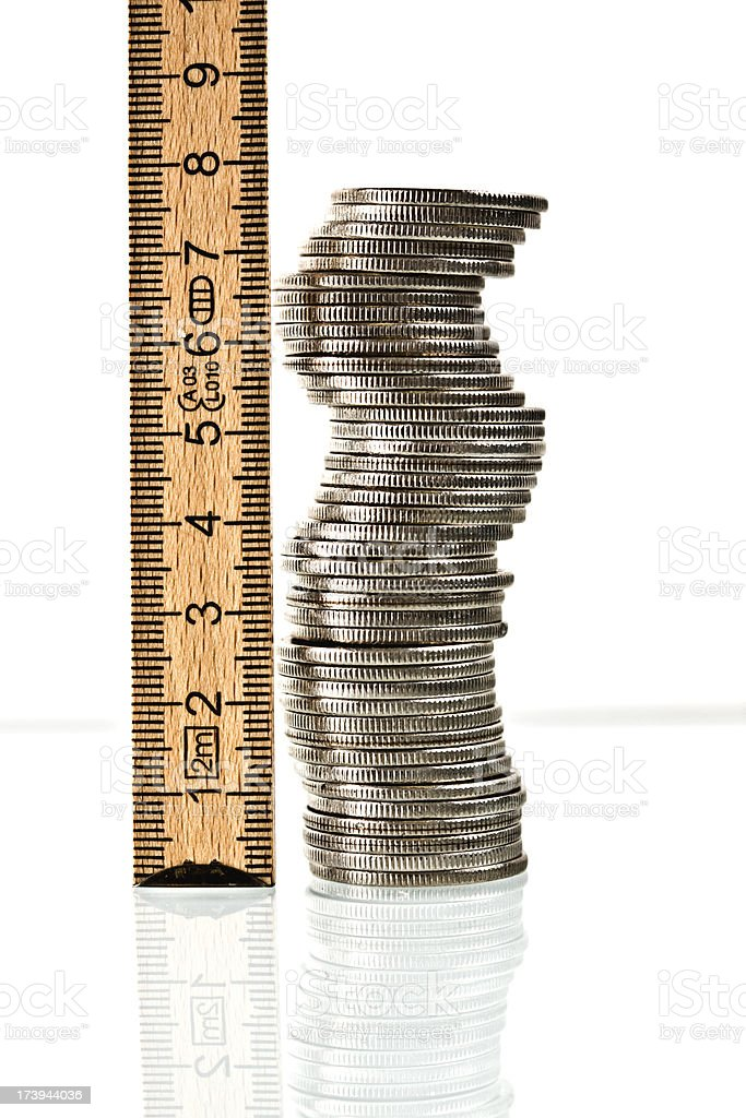 Measure your money concept with a ruler and a pile of coins stock photo