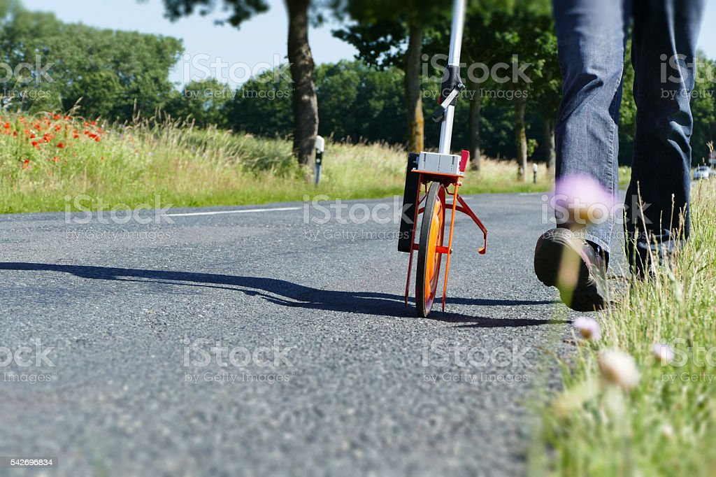 measures road with distance measuring wheel stock photo