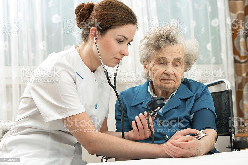 measuring blood pressure of senior woman stock photo