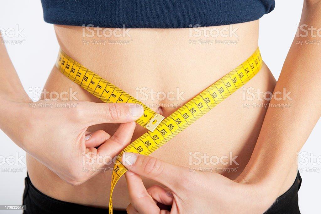 Measuring female slim waist using yellow tape measure stock photo