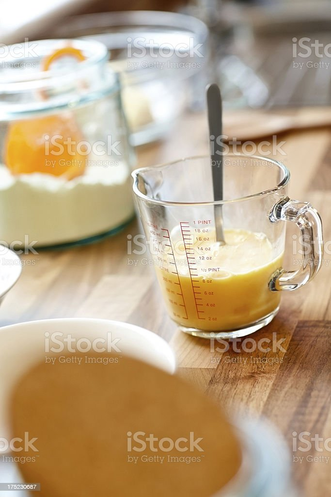 Measuring jar containing egg mix on kitchen counter royalty-free stock photo