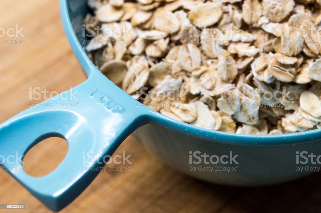 Measuring One Cup of Traditional Jumbo Rolled Oats royalty-free stock photo