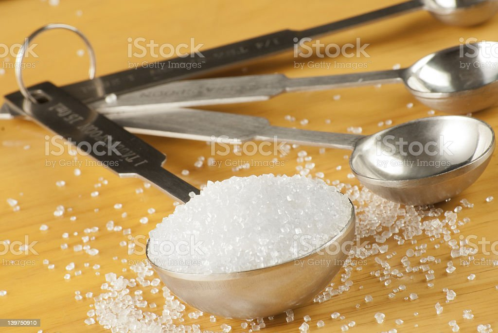Measuring spoon full of sugar stock photo