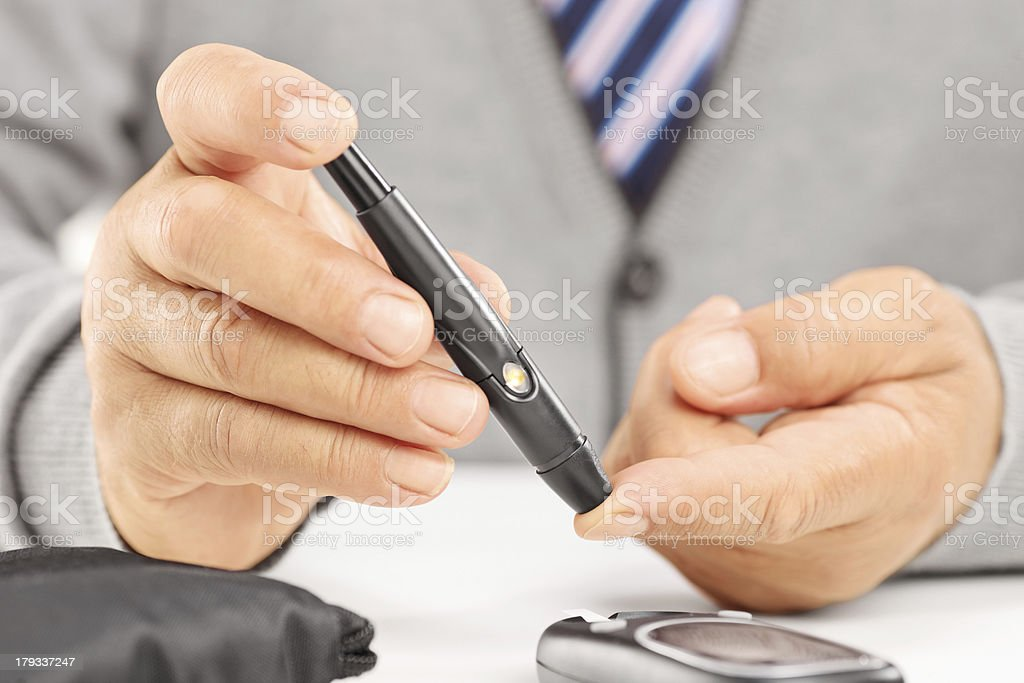 Measuring sugar level in blood using glucometer stock photo