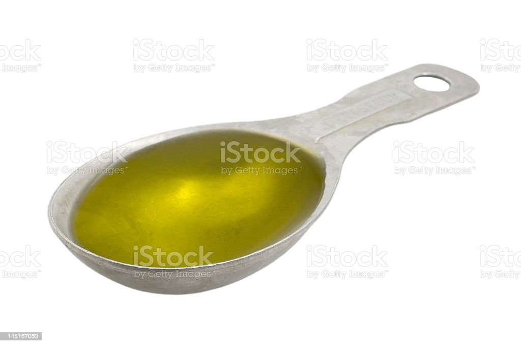 Measuring tablespoon of olive oil stock photo