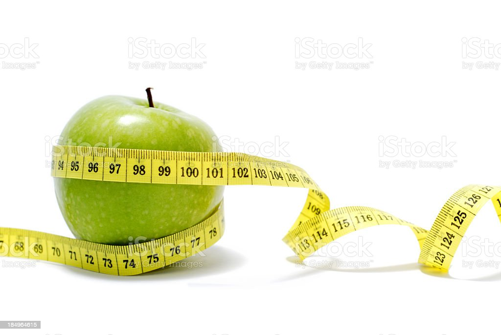 A measuring tape around a Granny Smith Apple isolated stock photo