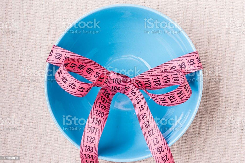 Measuring tape around empty bowl on table stock photo