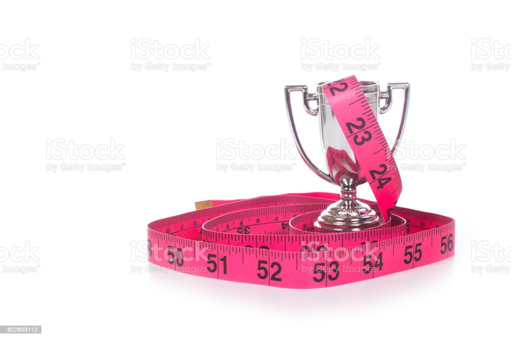 Measuring tape coiled around small sports cup stock photo