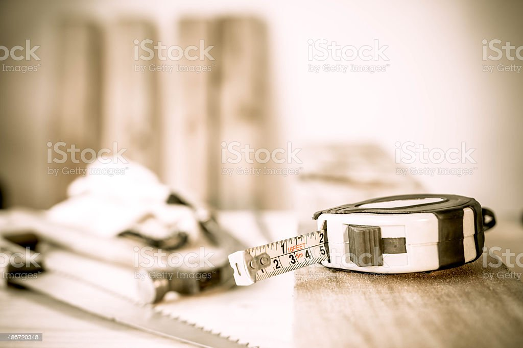 Measuring tape on a wood plank. Build concept. stock photo