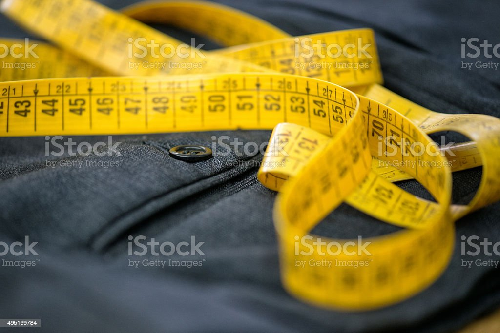 Measuring tape on pants in a tailor workshop stock photo