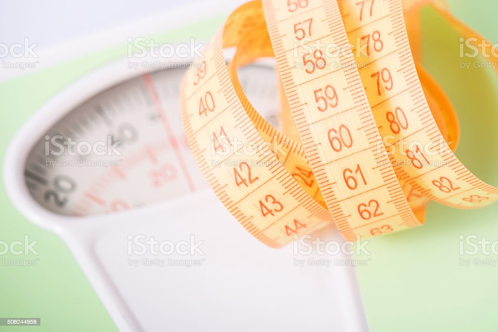 Measuring tape on top of scales stock photo