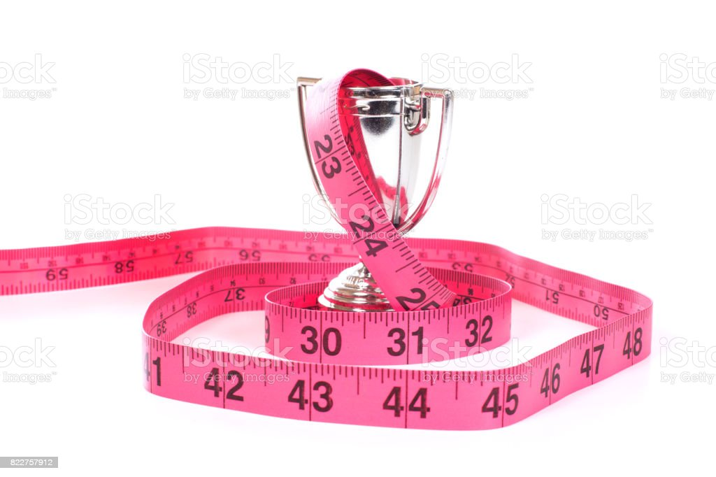 Measuring tape rolled around sports cup stock photo