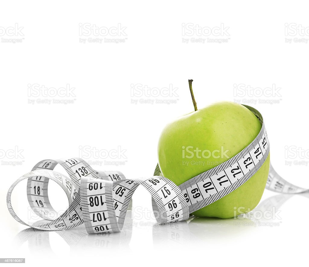 Measuring tape wrapped around a green apple stock photo